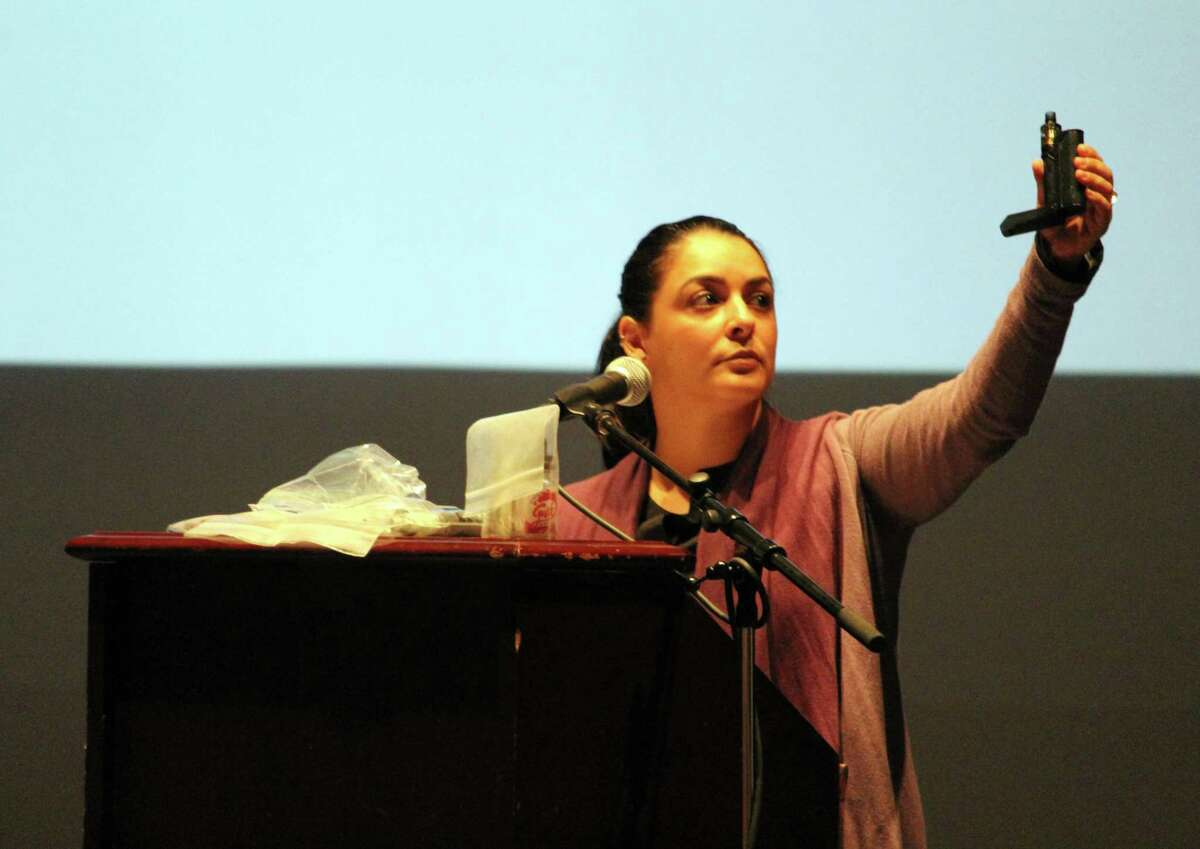 """Giovanna Pisani, director of Mid-Fairfield Substance Abuse Coalition, holds a vape device during Wednesday's panel discussion, """"Privileged and Pressured: How to Talk About Substance Abuse,"""" at Wilton High School."""