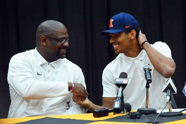 Edwardsville High School senior Mark Smith, right, is congratulated by his dad Anthony after announcing he will play college basketball for the University of Illinois in a ceremony.