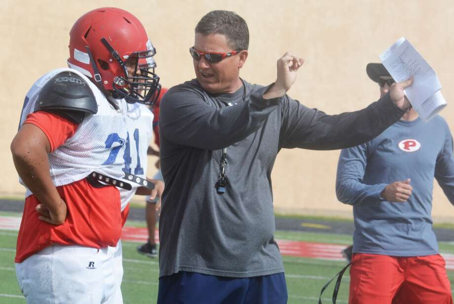 Plainview football head coach Ryan Rhoades demonstrates technique to a defensive lineman during spring practice this week. The Bulldogs are changing their offense and defense for next year, so the spring session is a time of learning for players and coaches. Photo: Skip Leon/Plainview Herald