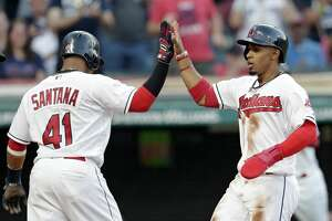 Cleveland Indians' Francisco Lindor, right, is congratulated by Carlos Santana after both score on a single hit by Cleveland Indians' Michael Brantley in the fifth inning of a baseball game, Wednesday, April 26, 2017, in Cleveland. (AP Photo/Tony Dejak)