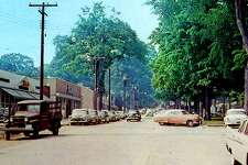 """The Village Green in New Milford is known for being picturesque. This postcard shows the west side of Main Street and the Village Green circa 1950s, with Slone's Pharmacy (and diner), Barton's Department Store, First National (not seen) and W.T. Grant store to the left. At the time, cars parked on both sides of the street, tall elm trees graced the Village Green and power poles and wires criss-crossed the streets. If you have a """"Way Back When"""" to share, contact Deborah Rose at drose@newmilford.com or call 860-355-7324."""