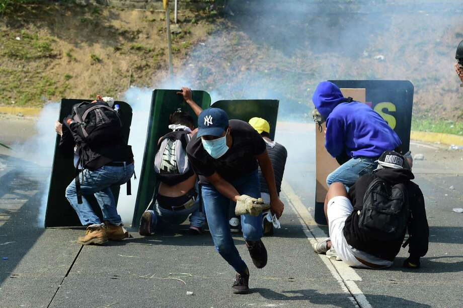 Opposition activists take cover behind advertisement placards as they clash with riot police during a protest march in Caracas on Wednesday. Photo: RONALDO SCHEMIDT, Staff / AFP or licensors