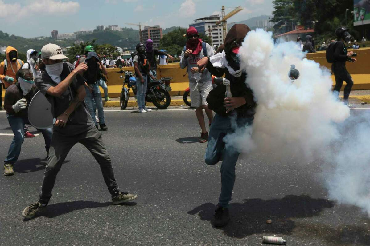An anti-government protesters is hit by a tear gas grenade launched by security forces in Caracas, Venezuela, Wednesday, April 26, 2017. Security forces blocked opponents of President Nicolas Maduro attempting to march to the Ombudsman's office in the capital's downtown in another day of protests that have already claimed dozens if lives since the start of April. (AP Photo/Fernando Llano)