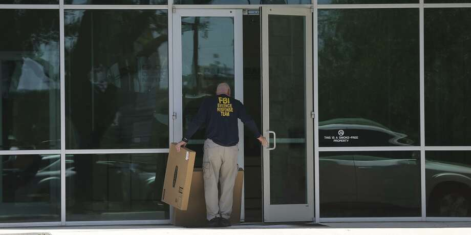 """A man wearing a shirt that reads """"FBI Evidence Response Team"""" walks Wednesday April 26, 2017 into the building located at 415 Embassy Oaks in San Antonio. A placard in front of the building was identified with the word """"Dannenbaum."""" According to the Laredo Morning Times website, the FBI has raided some city and county buildings in Laredo as well as Dannenbaum Engineering. Photo: John Davenport, STAFF / San Antonio Express-News / ©San Antonio Express-News/John Davenport"""