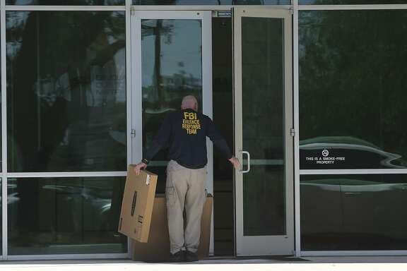 """A man wearing a shirt that reads """"FBI Evidence Response Team"""" walks Wednesday April 26, 2017 into the building located at 415 Embassy Oaks in San Antonio. A placard in front of the building was identified with the word """"Dannenbaum."""" According to the Laredo Morning Times website, the FBI has raided some city and county buildings in Laredo as well as Dannenbaum Engineering."""