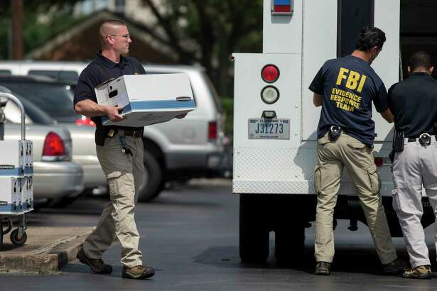 FBI officers collect evidence from the Dannenbaum Engineering firm at 3100 W. Alabama St. in Houston on Wednesday. The FBI also raided the company's locations in San Antonio, McAllen, and Laredo.