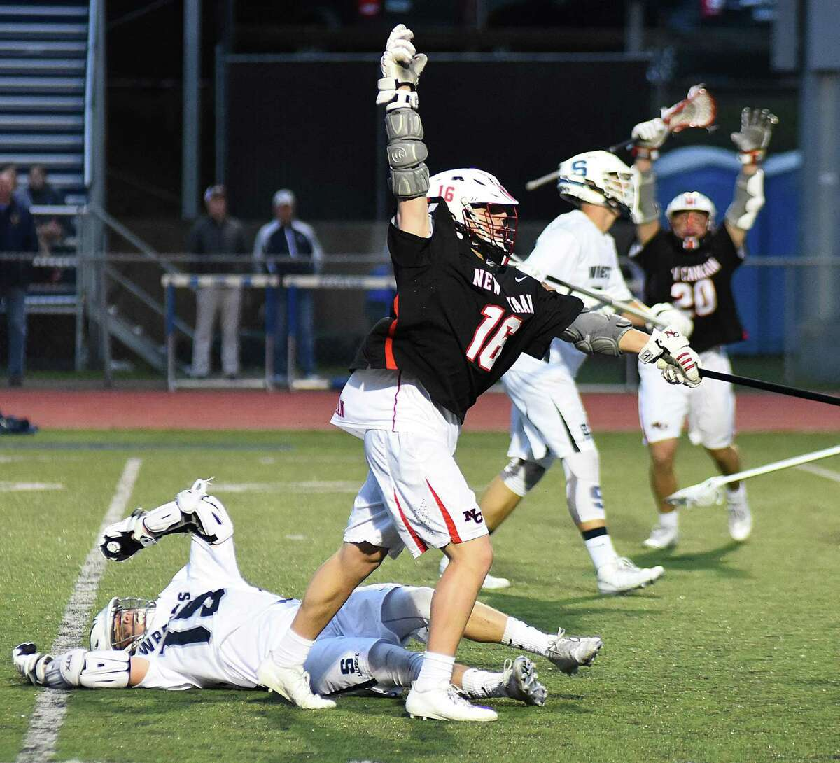New Canaan's Graham Braden, center, reacts after scoring the game-winning goal with four seconds left in the second overtime during the Rams' 15-14 FCIAC boys lacrosse win over Staples in Westport on Wednesday night.