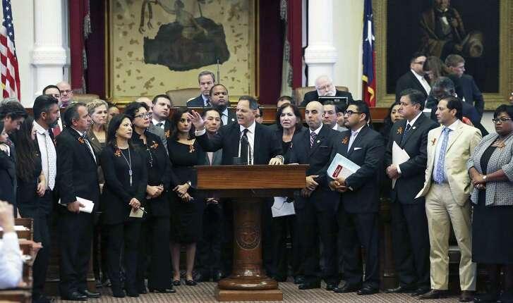 Representative Rafael Anchia leads a group of legislators at the podium protesting proposed sanctuary city legislation  in the House of Representatives debate  on April 26, 2017.