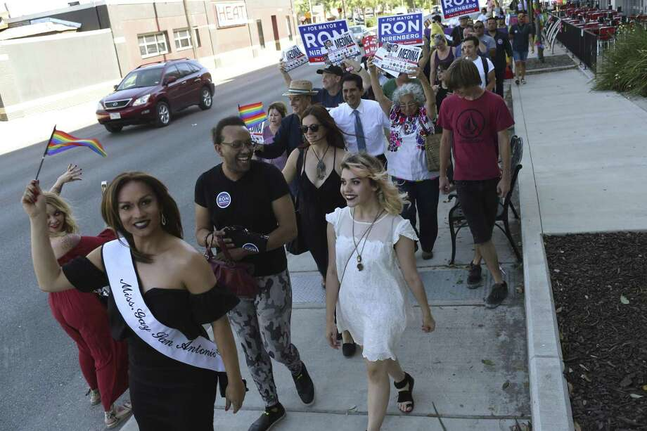 Miss Gay San Antonio Aaron Andrews, and Clark High School senior Sloan Martin, 18, center right in white, lead the March for Mayor on Main, Wednesday, April 26, 2017.  Martin organized the march to bring awareness to the LGBTQ community and increase the LGTBQ vote. Of the three top candidates, Mayor Ivy Taylor decline the invitation, Ron Nirenberg had a prior engagement but sent staff. Only Manuel Medina attended. The group gathered at Luther's Cafe on North Main Street and marched to the William R. Sinkin Eco Center polling site a few blocks away where several, including Martin, voted. Photo: JERRY LARA / San Antonio Express-News / © 2017 San Antonio Express-News