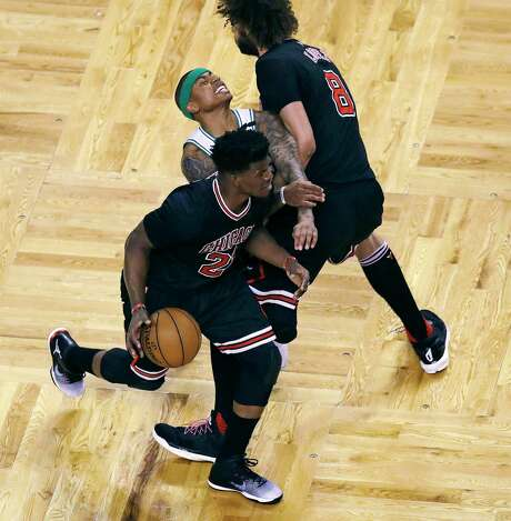 The Celtics' Isaiah Thomas, center, gets caught in a squeeze play between a driving Jimmy Butler, left, and a screening Robin Lopez. Photo: Charles Krupa, STF / Copyright 2017 The Associated Press. All rights reserved.