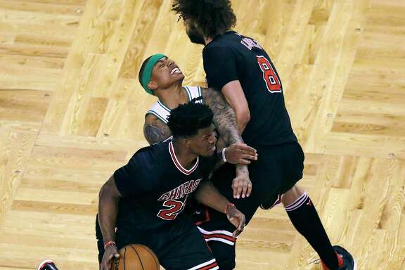 The Celtics' Isaiah Thomas, center, gets caught in a squeeze play between a driving Jimmy Butler, left, and a screening Robin Lopez.