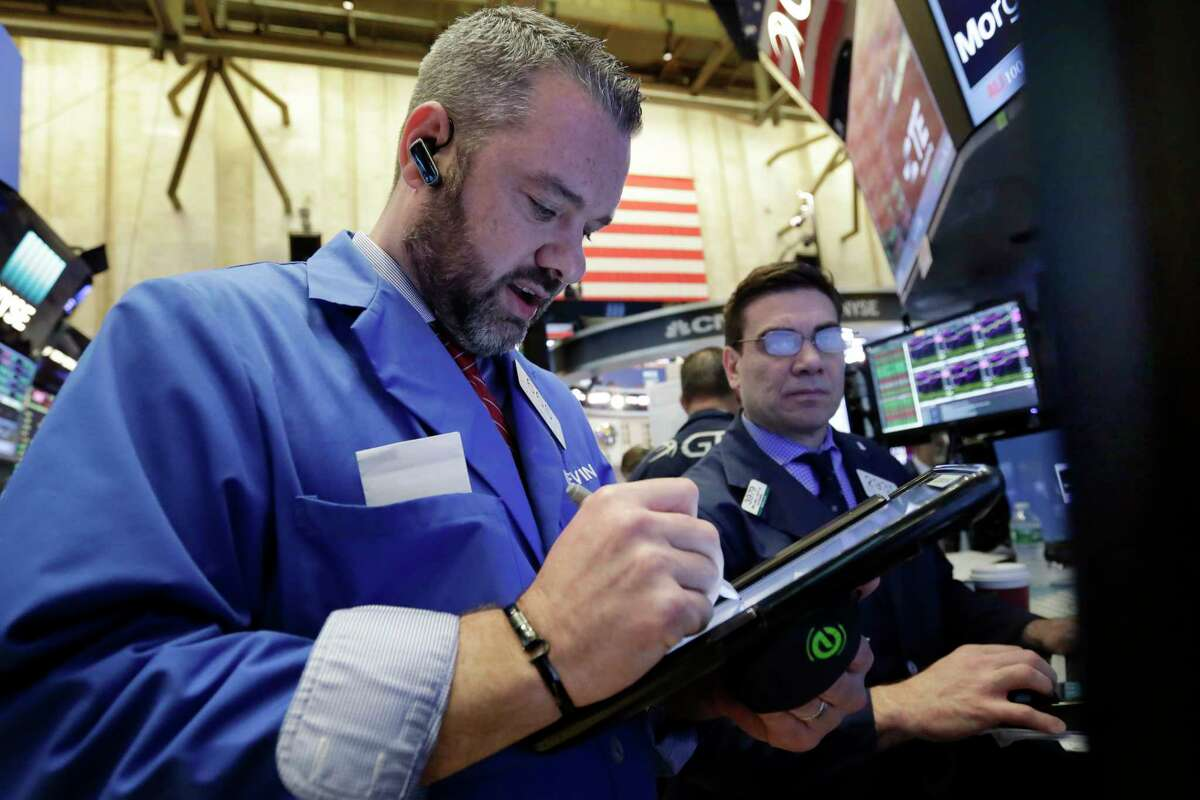 Trader Kevin Lodewick, left, works on the floor of the New York Stock Exchange, Wednesday, April 26, 2017. Stock markets around the world made only modest moves on Wednesday, waiting to see what the White House has in store for U.S. tax policy. (AP Photo/Richard Drew)
