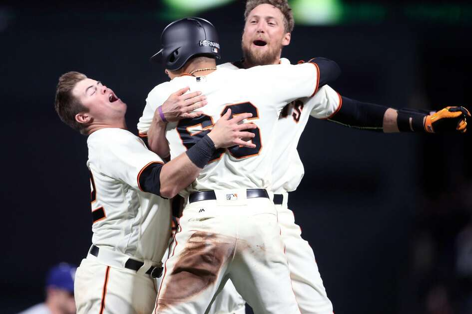 San Francisco Giants' Hunter Pence celebrates his 10th inning game-winning sacrifice fly with Christian Arroyo and Gorkys Hernandez after 4-3 win over Los Angeles Dodgers during MLB game at AT&T Park in San Francisco, Calif., on Wednesday, April 26, 2017.
