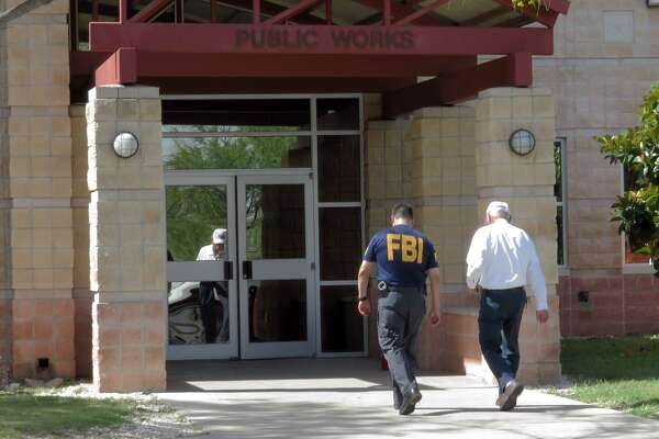 A man is escorted into the Public Works department offices by an FBI agent Wednesday, April 26, 2017 after FBI and Texas Department of Public Safety personnel closed the offices.