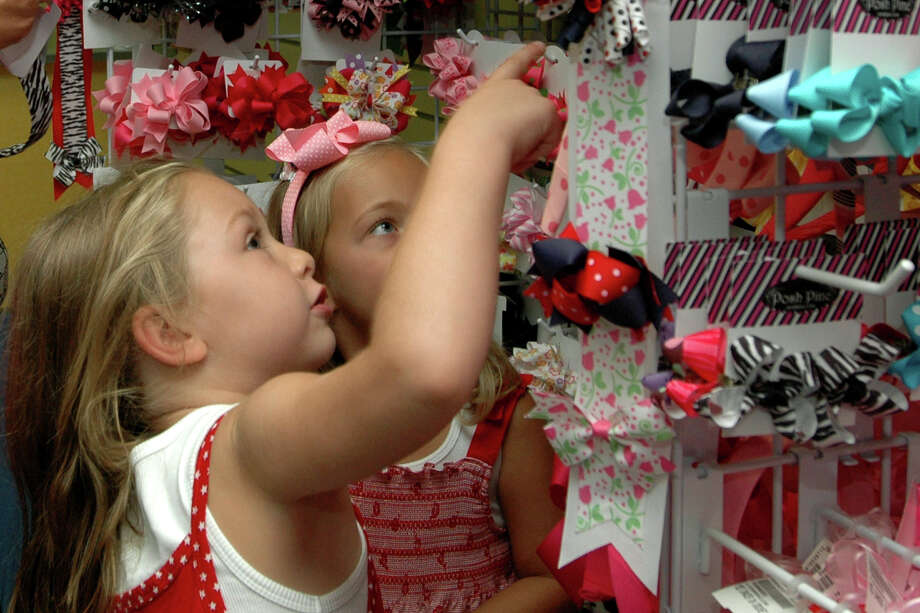 Girls shop for headbands and bows at Once upon a Child in San Antonio. (PHOTO BY BETH SPAIN/San Antonio Express-News) Photo: BETH SPAIN, SPECIAL TO THE EXPRESS-NEWS / SAN ANTONIO EXPRESS-NEWS