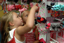 Madisen Sanders, 6, and her sister Maeghan Sanders, 5, shop for headbands and bows at Once upon a Child, a 5,000 SF resale shop for children's items, that opened last Thursday, July 9. The franchise from Winmark Corp. plans to open numerous resale stores in San Antonio including junior clothing, musical instruments & sports gear. (PHOTO BY BETH SPAIN/San Antonio Express-News)