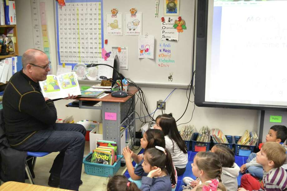 Stamford Media Center Senior Director Adam Sorota reads to a first-grade class at Toquam Magnet Elementary School in Stamford on Tuesday. Photo: Contributed