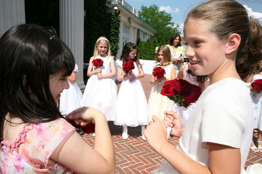 Convent of the Sacred Heart second-graders Renata Trevino, left, and Katie Keller wait for the start of Friday afternoon's commencement ceremony in which they handed each of the graduates a small bouquet of roses. Photo: David Ames, David Ames/For Greenwich Time / Greenwich Time
