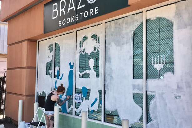 "Artist Jade Young, who works under the name Jade O'Lantern, paints the front window at Brazos Bookstore for the ""Summer of Austen."" A reception Saturday will introduce the three-month celebration of Jane Austen."