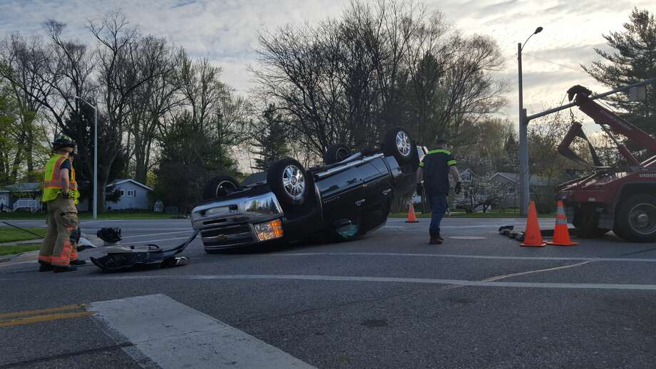 The intersection of Saginaw and Sugnet roads was closed for about an hour this morning after a crash. The crash, involving a small white pickup truck and a black Chevrolet Silverado, left the Chevy upside down in the intersection. Photo: Daily News Photo By Kelly Dame