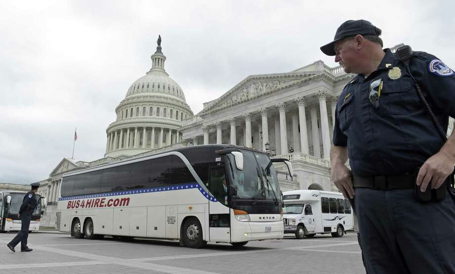 Capitol Hill police officers guard a bus for senators that headed to the White House for a briefing about North Korea. Photo: Susan Walsh /Associated Press / Copyright 2017 The Associated Press. All rights reserved.
