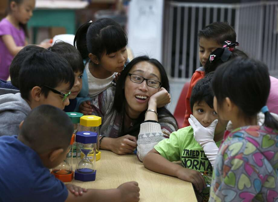 Above: Sarah Barbo teaches prekindergarten students at the Mission Child Care Consortium in S.F. Below: Gisele Loyola says she can work thanks to affordable child care for daughter Leticia Pinheiro. Photo: Paul Chinn, The Chronicle