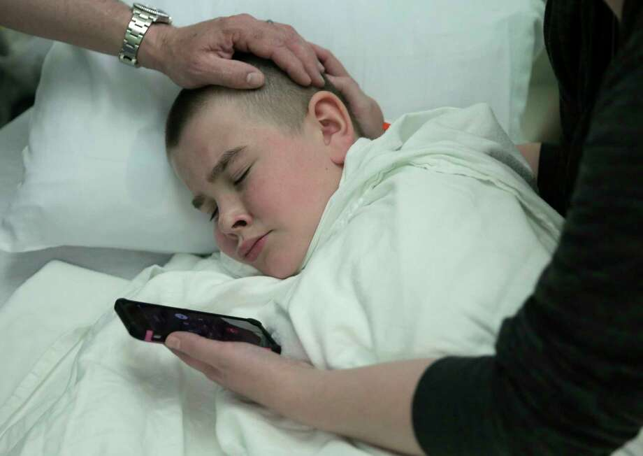 Brayden Large listens to his pastor, Justin Long, pray for him over the phone before his operation. Photo: Elizabeth Conley, Houston Chronicle / © 2017 Houston Chronicle
