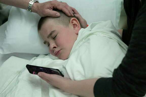 Brayden Large listens to his pastor Justin Long, pray for him over the phone before his operation.