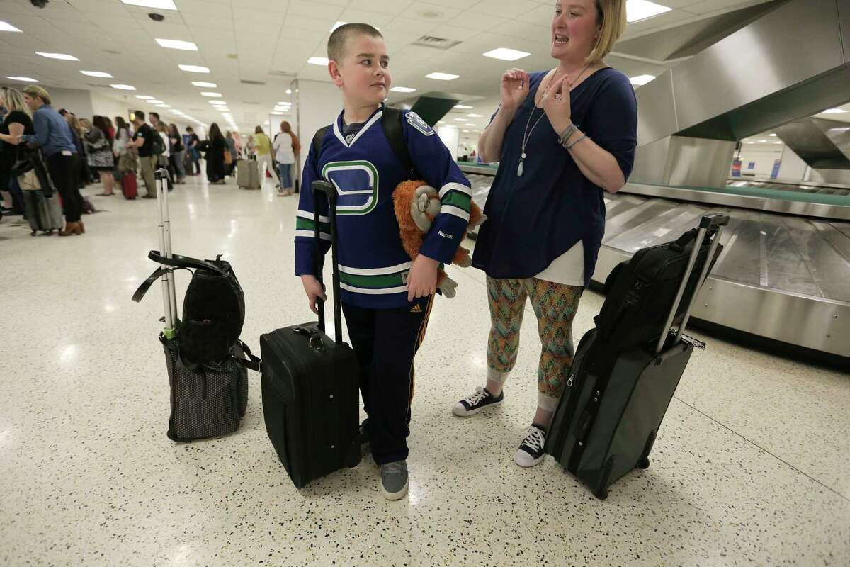 Brayden, 11, waits for luggage with his mom, Jessica, after arriving at George Bush Intercontinental Airport two days before his scheduled brain surgery.