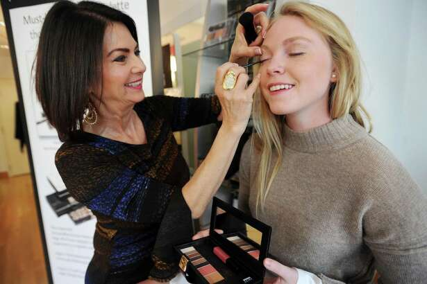 Cosmetics entrepreneur Gail Sagel demonstrates her newest product, Face in a Case, a portable make-up case that doubles as a wallet, on Maggie Walsh, of Westport, at her Faces Beautiful salon in Westport, Conn. on Wednesday, April 26, 2017.
