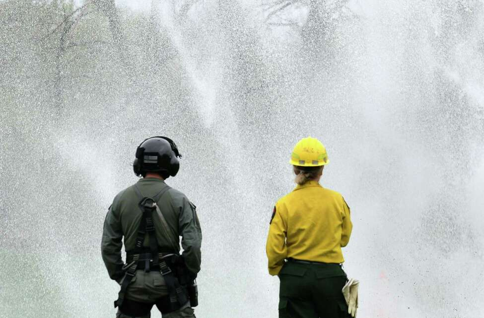 New York State Forest Ranger Sarah Bode, right, trains with fellow ranger Ian Kerr, left, as water is dropped from a state police helicopter during a water-bucket drop training exercise on Thursday, April 27, 2017, at the Mohawk View Water Treatment Plan in Colonie, N.Y. Rangers practiced guiding in the helicopter for an effective water dispersion drop. (Will Waldron/Times Union)