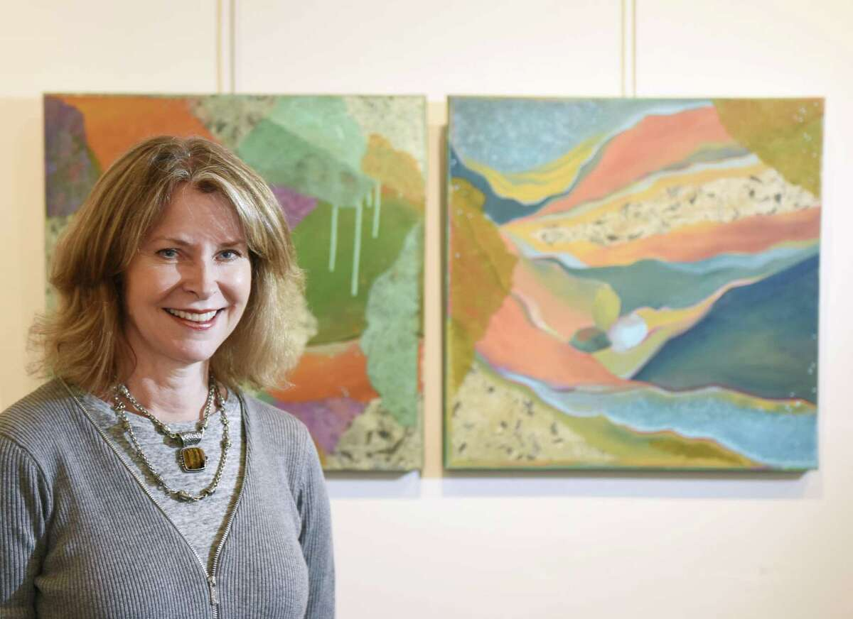 """Heidi Lewis Coleman poses as her first-place painting's Tide Pool,"""" left, and """"Valyria are displayed in the 18th Annual Vivian & Stanley Reed Marine Show at the Stamford Art Association Townhouse Gallery in Stamford, Conn. Wednesday, April 26, 2017. Artists of many mediums are showing their water-themed work in the show, opening Friday, April 28 at 6 p.m."""
