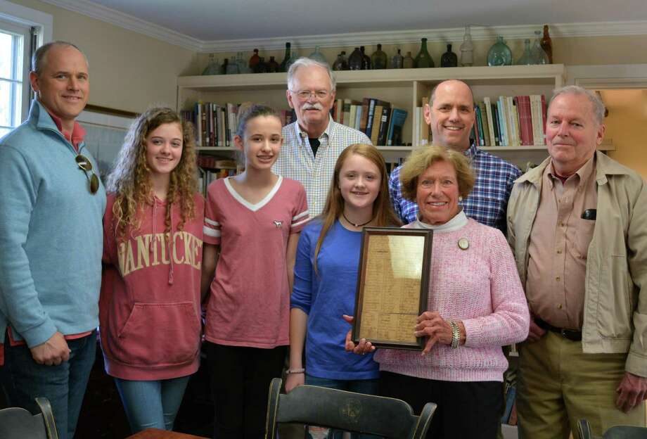 "The Burt family recently donated a Middlesex Militia muster roll from April of 1767, on the occasion of its 250-year anniversary to the Darien Historical Society. Pictured are Jeffrey Burt, Hattie Burt, Chloe Burt, Darien Historical Society historian Ken Reiss, Sophie Burt, Carolyn ""Rusty"" Burt (holding the document), Dave Burt, and Bill Ruscoe. Photo: Contributed Photo"