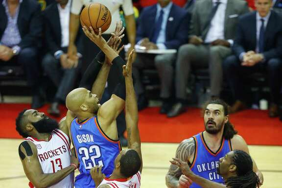 Oklahoma City Thunder forward Taj Gibson (22) tries to shoot over Houston Rockets forward Trevor Ariza (1) and Houston Rockets guard James Harden (13) during the first half of Game 5 of a Western Conference quarterfinals of the 2017 NBA playoffs, Tuesday, April 24, 2017, at Toyota Center in Houston. (Mark Mulligan / Houston Chronicle)