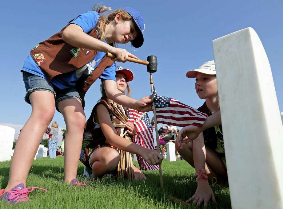 Troop 3161 Girl Scouts (from left) Ali Barnett, 9, Maegan Marfell, 9, and Abigail Ward, 9, place American flags at the headstones of fallen service members at Fort Sam Houston National Cemetery. A reader praises the article about five vets who received a final salute. Photo: Edward A. Ornelas /San Antonio Express-News / © 2016 San Antonio Express-News