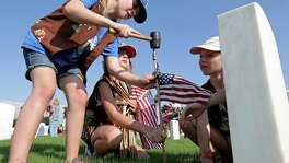 Troop 3161 Girl Scouts (from left) Ali Barnett, 9, Maegan Marfell, 9, and Abigail Ward, 9, place American flags at the headstones of fallen service members at Fort Sam Houston National Cemetery. A reader praises the article about five vets who received a final salute.