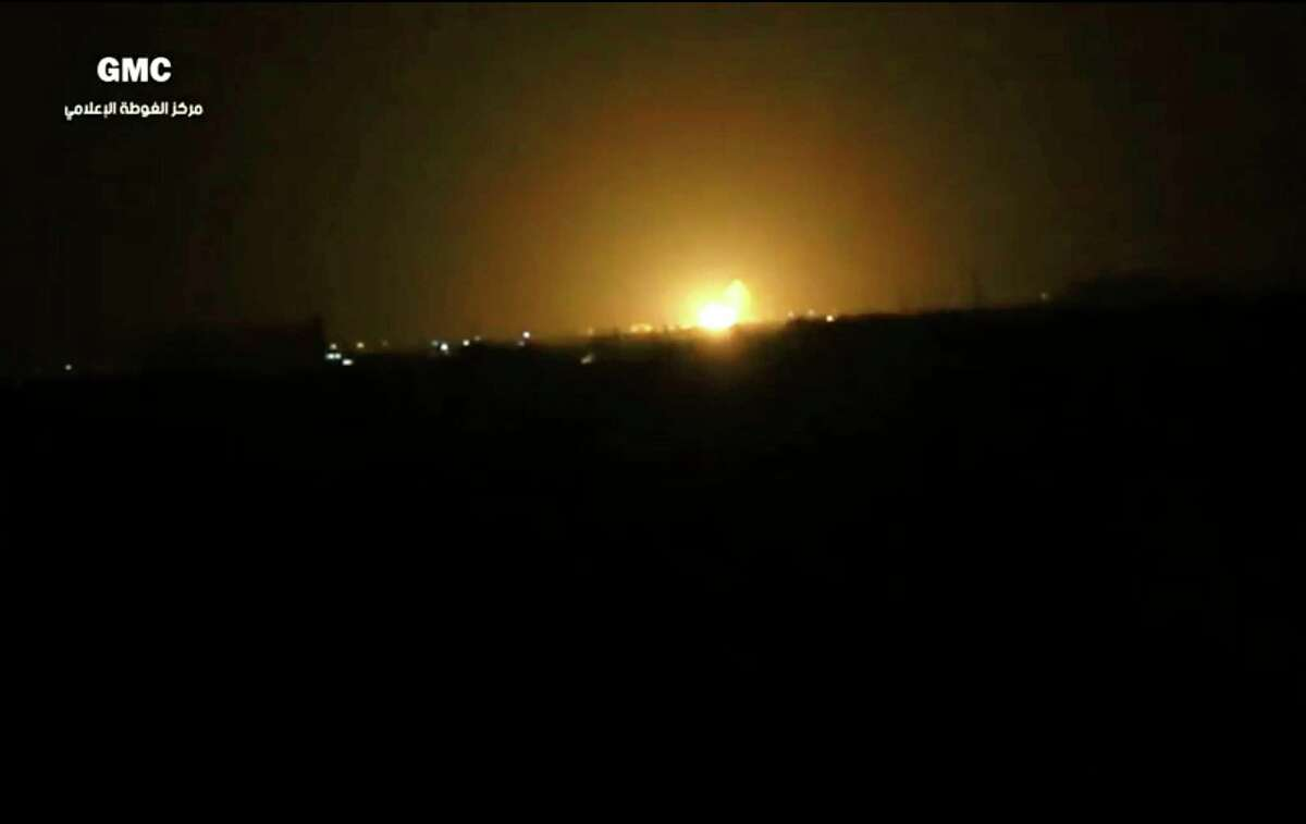 This frame grab from video provided by the Syrian anti-government group Ghouta Media Center shows flames rising after an explosion west of Damascus.