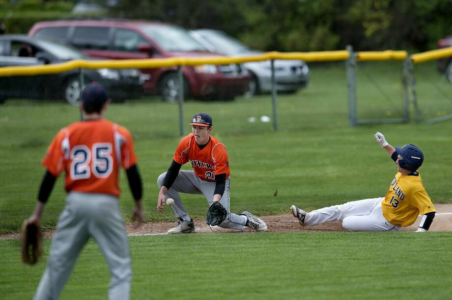 Midland High's Sam Vokal slides into third base before Flint Powers' Cam Conover can tag him out in the fifth inning of the Thursday afternoon game. Photo: Brittney Lohmiller/Midland Daily News/Brittney Lohmiller