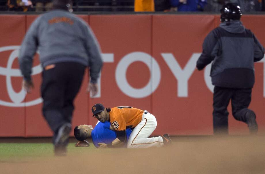 Former Giants outfielder Angel Pagan pins down Wayne Hsiung, whom he had body slammed to the ground, after Hsiung ran onto the field at AT&T Park during a September game. Photo: D. ROSS CAMERON, AP
