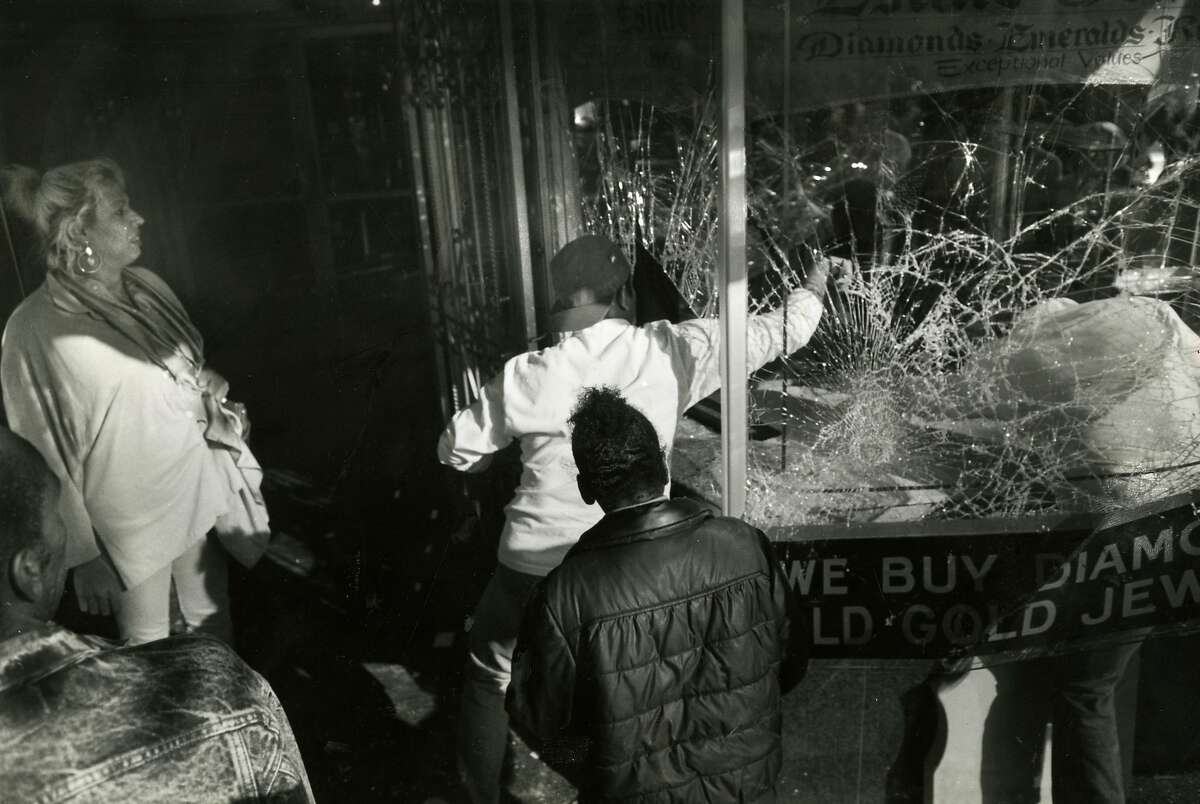 Looters making their way down Market St., breaking windows of a jewelry story and taking whatever they can get their hands on in this file photo from May 1, 1992.
