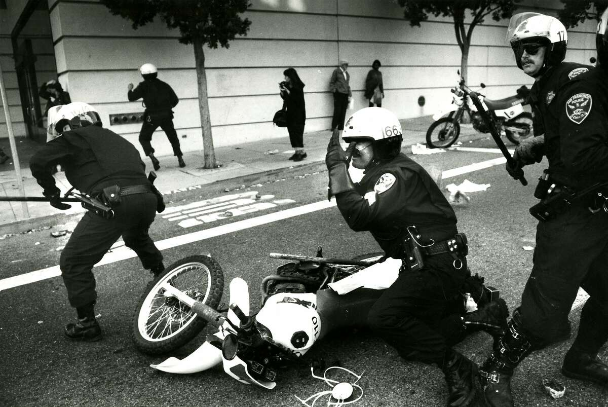 A San Francisco police officer gets knocked to the ground by demonstrators, and received help picking himself up by fellow officers in this file photo from May 1, 1992.
