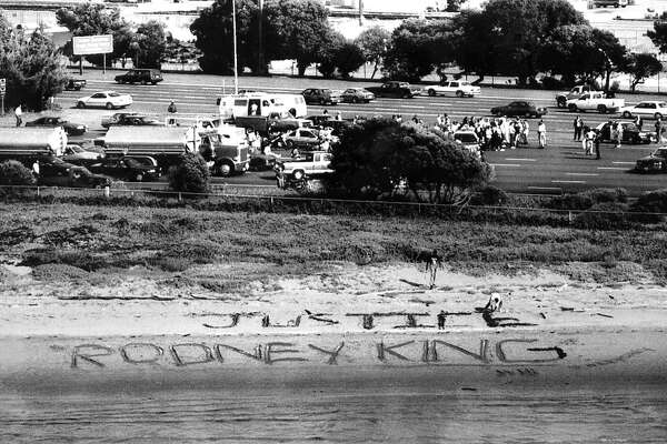 Bay Bridge closure, by protesters over Rodney King decision, the incline section, CHP arrest people who blocked the bridge. Message carved in the sand at the toll plaza. May 2, 1992.