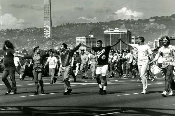 A line of Berkeley students lead the protesters against traffic on I-80 heading toward toll plaza. May 1, 1992.