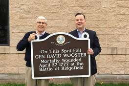Director of Parks and Recreation Paul Roche and state Rep. John Frey hold the newly restored historical marker sign honoring General Wooster who died in the Battle of Ridgefield.