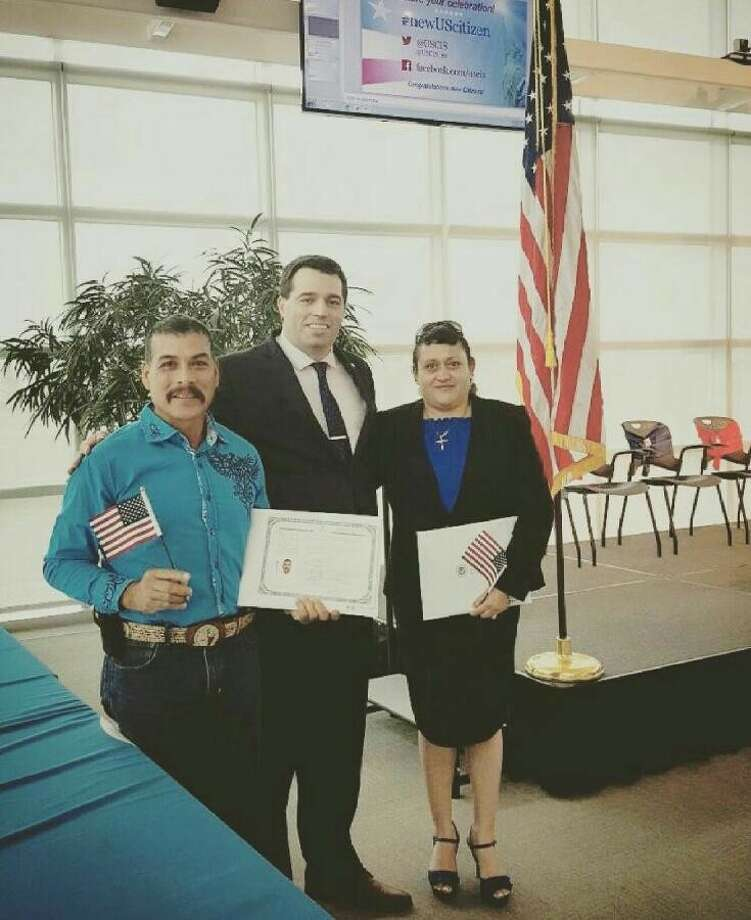 Plainview residents Luis (left) and Maria Martinez hold miniature American flags along with their U.S. citizenship papers after receiving them at a naturalization ceremony April 13 at the U.S. Citizenship and Immigration Services district office in Irving. They are shown withSupervisory Immigration Services Officer Raul Maus.