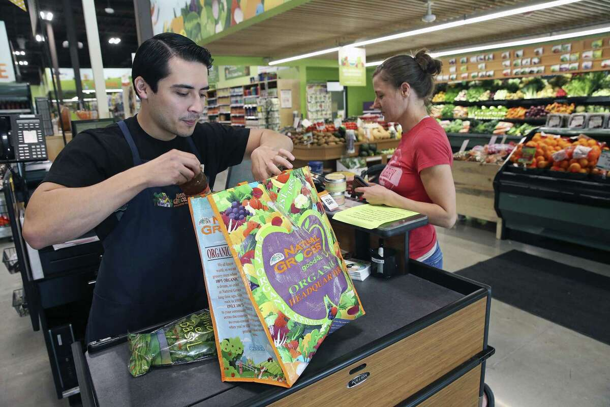 Cashier Arnoldo Crispin bags some items for Amanda Cavanaugh at the new Natural Grocers store at 6514 N. New Braunfels Ave.