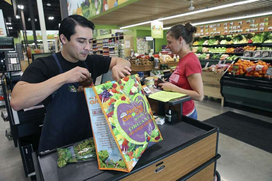 Cashier Arnoldo Crispin bags some items for Amanda Cavanaugh at the new Natural Grocers store at 6514 N. New Braunfels Ave. Photo: Tom Reel /San Antonio Express-News / 2017 SAN ANTONIO EXPRESS-NEWS