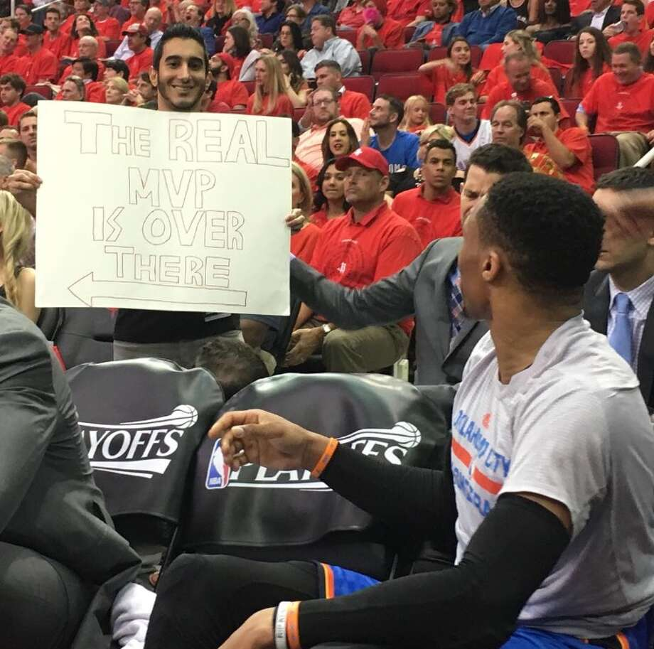 "Houston Rockets fan Keeyan Sabz holds up a sign behind the NBA's 2016-17 likely  Most Valuable Player, Russell Westbrook of the Oklahoma City Thunder, Tuesday April 24, 2017, during the Rockets playoff victory over the Thunder at Toyota Center. The sign, which says ""The real MVP is over there,"" points toward Rockets guard James Harden. (Photo: Keeyan Sabz)"