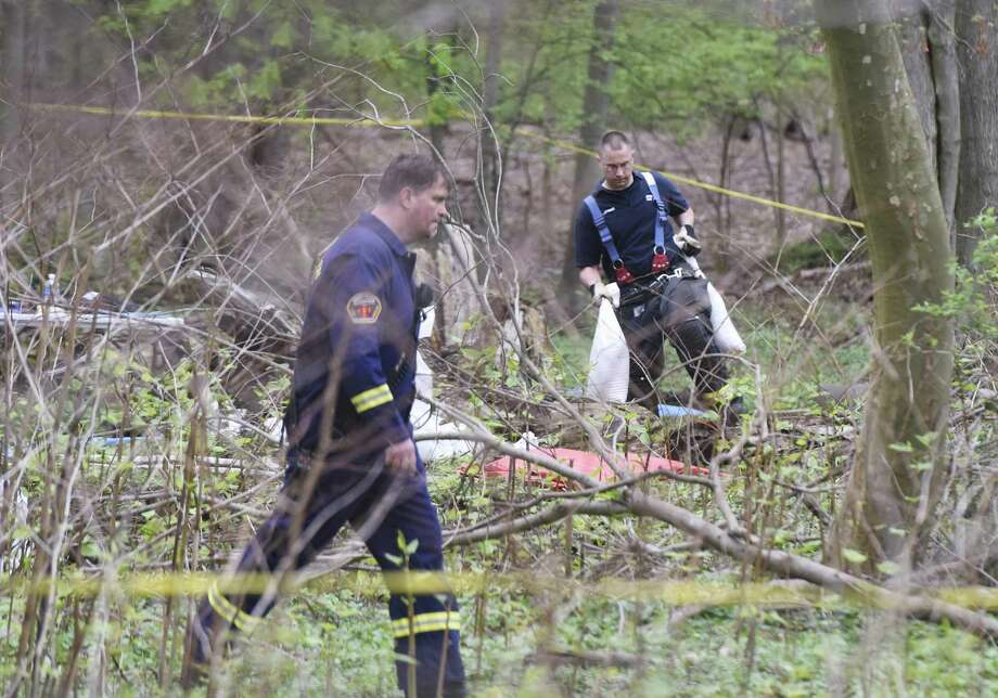 A firefighter carries equipment to the scene where local and state authorities are expanding their investigation from Wednesday's finding of human remains in Helen Binney Kitchel Natural Park in Old Greenwich, Conn. Thursday, April 27, 2017. Town employees clearing debris found human remains Wednesday and the area remained taped off as canvassing of the scene continued Thursday. Photo: Tyler Sizemore / Hearst Connecticut Media / Greenwich Time