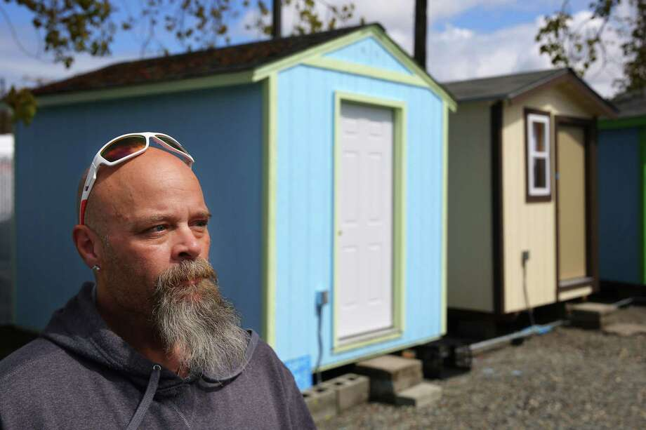 """Chad Woods and his wife Donna were on their way to Seattle from Texas following promises of a new job and place to live when they found out the job fell through and they were left homeless. After living in Tent City 3 for a short time, they recently moved into the new Georgetown tiny house village. """"It's a full time job being homeless,"""" says Woods. They have since been able to get steady jobs at Microsoft and working concessions the stadiums. The Georgetown village opened March 2. Photo: GENNA MARTIN, SEATTLEPI.COM / SEATTLEPI.COM"""